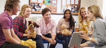 Teacher Helping Students Taking Childcare Course Holding Soft Toys And Digital Tablet