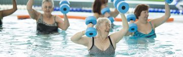 A multi-ethnic group of senior adults are taking a water aerobics class at the public pool. They are holding water weights and are working out.